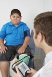 安排的男孩他的血液压力被检查 免版税库存图片
