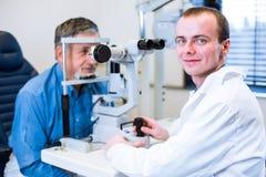 安排的老人他的眼睛审查由眼科医生 免版税图库摄影