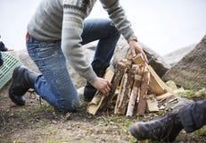 安排篝火的人木柴在湖边野营 免版税库存照片