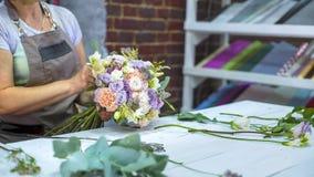 安排花婚礼花束的专业卖花人在有赠送阅本空间的花卉设计演播室 库存图片