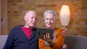 安排资深灰发的白种人的夫妇网上录影拜访是的片剂愉快和快乐的在舒适家 股票录像