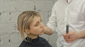 安排年轻美丽的妇女她的头发被剪在美发师的 股票录像
