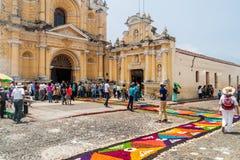安提瓜,危地马拉- 2016年3月27日:人们沿在圣佩德罗Apostol教会前面的装饰复活节地毯进来 库存图片