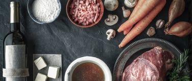 安格斯牛肉、青葱、红萝卜、蘑菇、烟肉、黄油、面粉、大蒜、汤和酒在老木台式视图 库存图片