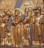 安特卫普- Cyrene的西蒙帮助耶稣运载他的十字架。金属化安心作为从Joriskerk或圣乔治储的发怒方式周期一部分 免版税库存照片