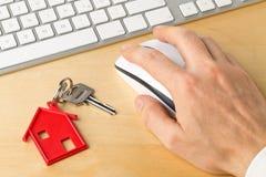 安置与红色房子钥匙链垂饰和计算机键盘的门钥匙 库存照片