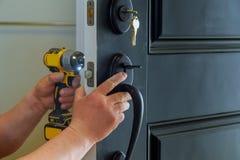 安置与锁的里面内部零件的外门安装或修理新的d的可看见一位专业锁匠 免版税图库摄影