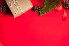 安置了礼物盒、干杉木和杉木叶子 作为圣诞节的一个概念在红色背景 免版税库存图片