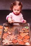 安置圣诞节曲奇饼的小女孩在盘子 免版税库存图片