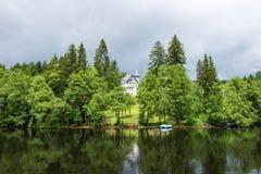 安置在森林附近的湖后的屋顶在Titisee诺伊施塔特,德国 免版税库存照片