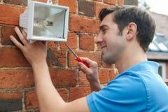 安置墙壁的人贴合安全光 免版税图库摄影