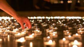 安置她的在其他蜡烛之间的妇女蜡烛 免版税库存照片