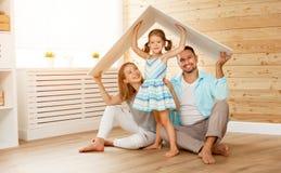 安置年轻家庭的概念 母亲父亲和孩子新的h的 免版税库存照片