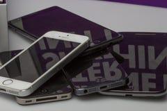 安置智能手机一个到另一个,放置在桌边只是可看见的 图库摄影