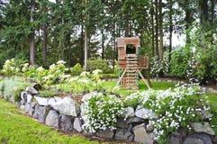 安置有岩石墙壁的春天后院并且开玩笑操场。 免版税库存照片