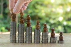 安置棋子的商人的中央部位在被堆积的硬币 免版税库存照片