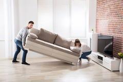 安置沙发的夫妇在他们新的家 免版税库存照片
