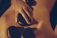 安置热的石头的女按摩师在妇女的  库存照片