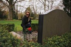 安置玫瑰的少妇在公墓 免版税库存图片