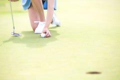 安置球的妇女的低部分在高尔夫球场 库存照片