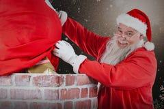 安置礼物盒的圣诞老人的综合图象入烟囱 免版税库存照片