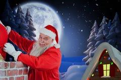 安置礼物盒的圣诞老人的综合图象入烟囱 免版税图库摄影