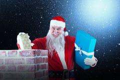 安置礼物盒的圣诞老人画象的综合图象入烟囱 免版税库存照片