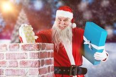 安置礼物盒的圣诞老人画象的综合图象入烟囱 库存图片