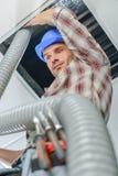 安置管子的建筑工人 库存照片
