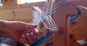 安置羊毛螺纹的资深妇女在织机4k 影视素材