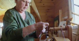 安置羊毛螺纹的资深妇女在织机4k 股票录像