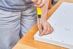 安置者螺旋连接家具螺丝到白色粗纸板里 免版税库存图片
