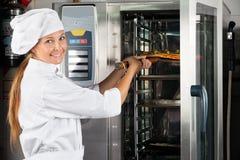 安置薄饼的厨师在烤箱 库存图片