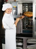 安置薄饼的女性厨师在烤箱 免版税库存图片