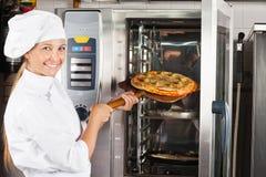 安置薄饼的美丽的厨师在烤箱 库存照片