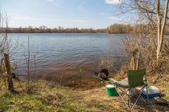 安置钓鱼者在河岸在一个清楚的晴天在春天 钓鱼竿,钓鱼位子,坦克,箱子诱剂 概念  库存图片