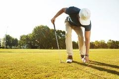 安置高尔夫球的年轻男性高尔夫球运动员在发球区域 免版税库存照片