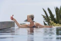 安置代基里酒的妇女在游泳池边 库存照片