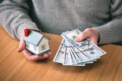 安置货币 买房地产,房屋贷款 拿着新的一百美元票据和玩具房子的手 库存照片