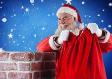 安置他的礼物大袋的圣诞老人入烟囱 库存照片