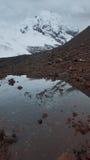 安蒂萨纳火山火山的看法,反映在一个盐水湖在安蒂萨纳火山生态储备的一多云天 免版税库存图片