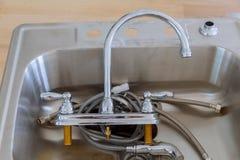安装一个不锈钢厨房水槽 免版税库存图片
