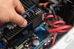 安装一个新的图形卡GPU的技术员的手在个人计算机, 图库摄影