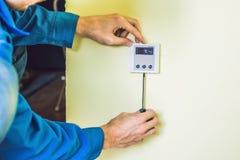 安装一个电子温箱的电工在一个新房 免版税库存照片