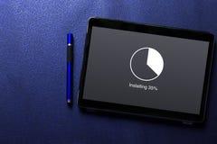安装与圈子的更新装载百分比等待指示器概念在片剂屏幕用在蓝色样式的蓝色笔 免版税库存图片