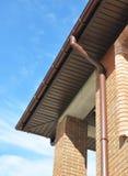 安装与塑料外部房屋板壁下端背面和的房檐的排水系统 免版税库存图片