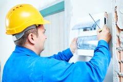 安装交换的电作动器的电工在保险丝箱子 库存照片