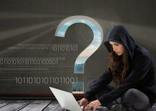 安装和研究一台膝上型计算机的妇女黑客有与问号的灰色背景 免版税库存图片
