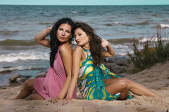 安装在沙子的两名妇女在海附近 库存图片