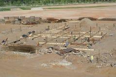 安装地梁模板的建筑工人 免版税库存图片